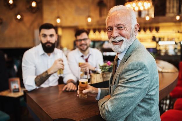 Drei geschäftsleute jubeln beim fußballspiel in einer café-bar. Premium Fotos