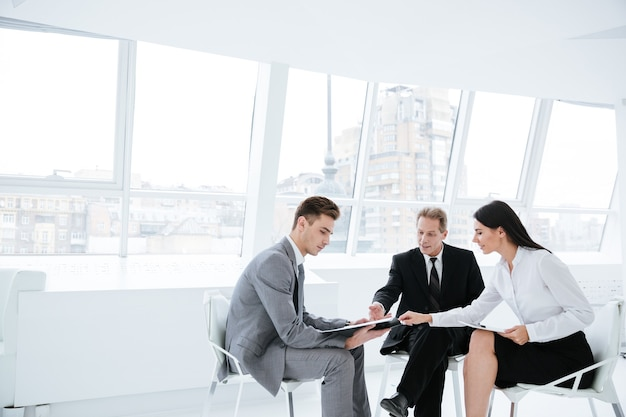 Drei geschäftsleute sitzen auf stühlen mit dokumenten am fenster im konferenzraum