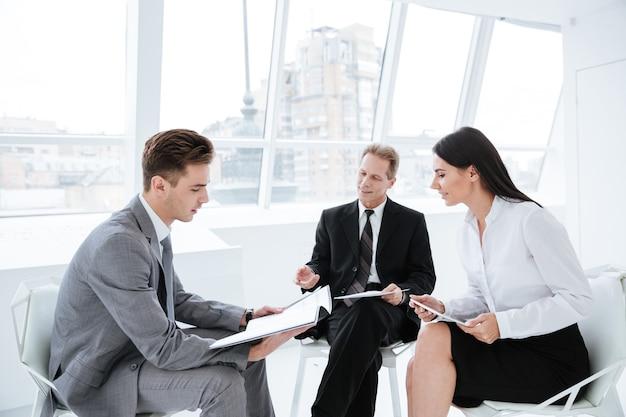 Drei geschäftsleute sitzen auf stühlen mit dokumenten im konferenzraum
