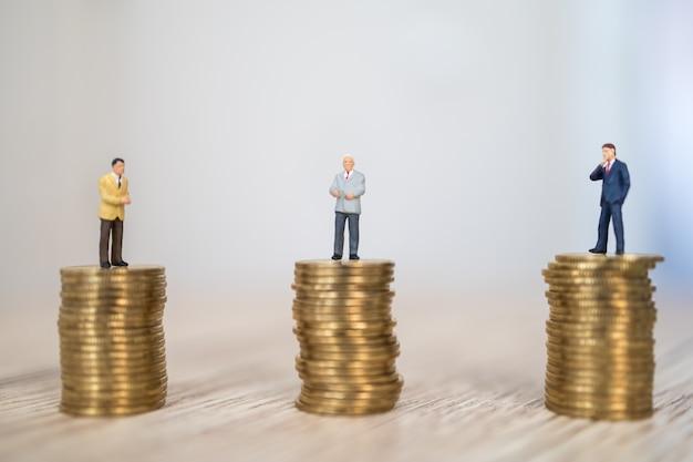 Drei geschäftsmann-miniaturfigurmenschen, die auf stapel von goldmünzen auf holztisch stehen.