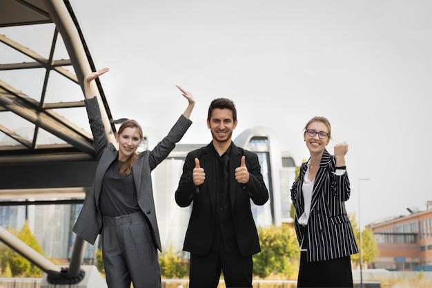 Drei geschäftspartner stehen vor dem hintergrund eines bürogebäudes. sie freuen sich und lächeln, als sie es geschafft haben, erfolgreich einen deal auszuhandeln und abzuschließen.