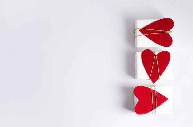 Drei geschenkboxen in weißem papier und mit herzen liegen auf einem weißen hintergrund.
