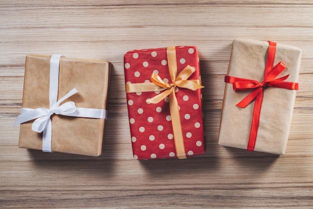 Drei geschenkboxen verziert mit satinbändern auf hölzernem hintergrund
