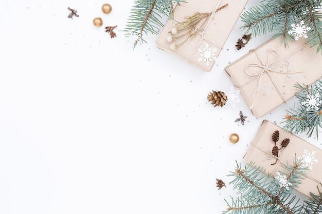 Drei geschenkboxen, weihnachtsschmuck, fichtenzweige auf weißem hintergrund. speicherplatz kopieren.
