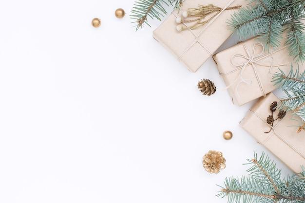 Drei geschenkboxen, weihnachtsschmuck, grüne zweige auf weiß