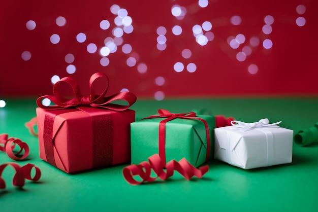 Drei geschenke serpentin und lichter bokeh auf rotem und grünem hintergrund feiertags- und weihnachtshintergrund