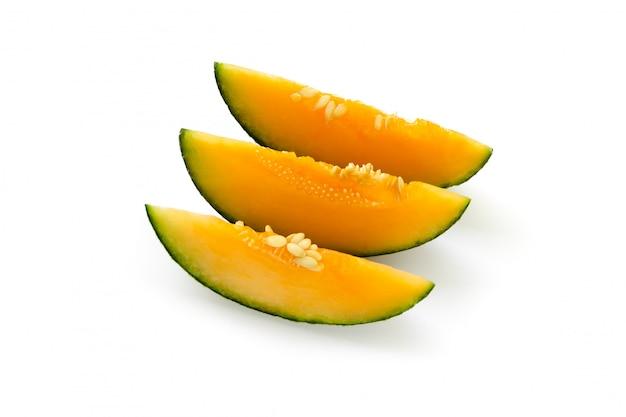 Drei geschnittene stücke gelbe melone. isoliert