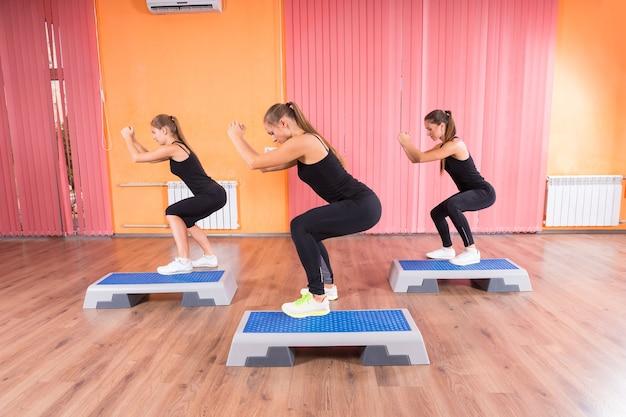 Drei gesunde frauen, die gleichzeitig kniebeugen mit aeroben step-plattformen im fitnessstudio machen.