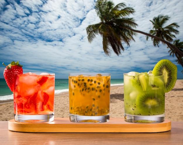 Drei getränke mit passionsfrucht, erdbeere und kiwi caipirinha im strandhintergrund