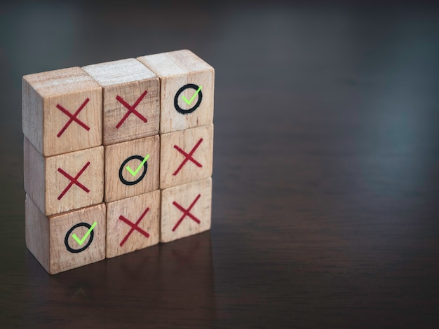 Drei gewinnende grüne häkchensymbole mit rotem kreuz auf tic-tac-toe-holzblockspiel, auf holztischhintergrund mit kopierraum. gewinner, strategie und geschäftszielkonzept.