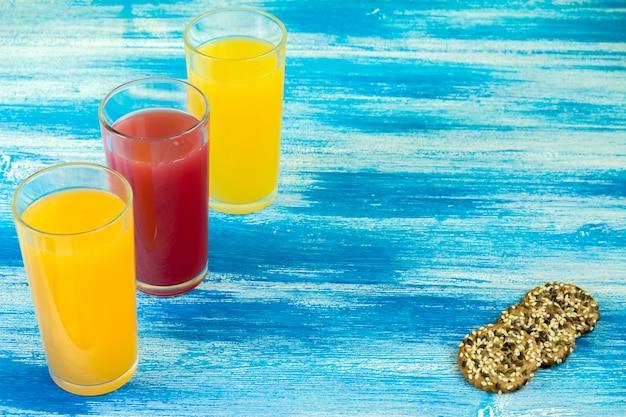 Drei gläser alkoholfreie getränke sind auf blauem grund
