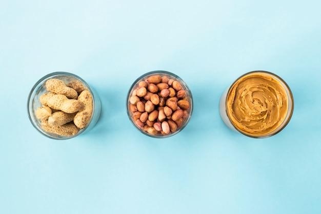 Drei gläser erdnuss in einer schale, geschälte erbsen und vegane erdnussbutter