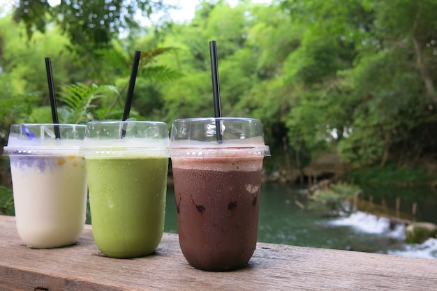 Drei gläser getränk - gefrorener kakao, grüner tee und frappe kokosnusssaft, der auf den holztisch setzt