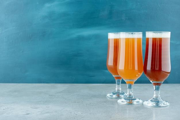 Drei gläser helles bier auf blau