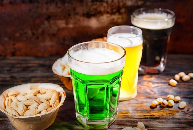 Drei gläser mit grünem, ungefiltertem und dunklem bier stehen in einer reihe neben tellern mit snacks und verstreuten nüssen auf einem dunklen holzschreibtisch. lebensmittel- und getränkekonzept