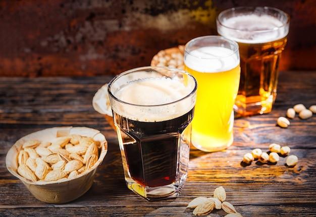 Drei gläser mit hellem, ungefiltertem und dunklem bier stehen in einer reihe neben tellern mit snacks und verstreuten nüssen auf einem dunklen holzschreibtisch. lebensmittel- und getränkekonzept