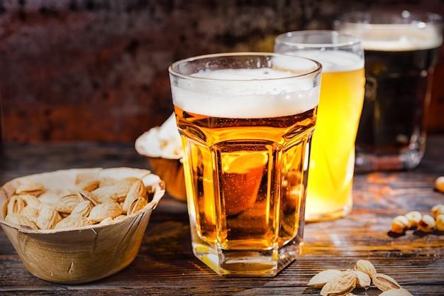 Drei gläser mit hellem, ungefiltertem und dunklem bier stehen in einer reihe neben tellern mit snacks und verstreuten pistazien auf einem dunklen holzschreibtisch. lebensmittel- und getränkekonzept