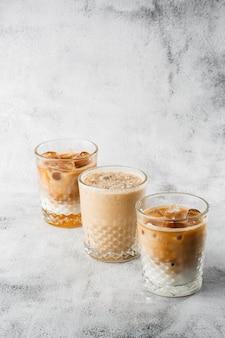 Drei gläser mit kaltem kaffee und milch und eiskakao lokalisiert auf hellem marmorhintergrund. draufsicht, speicherplatz kopieren. werbung für cafe-menü. coffeeshop-menü. horizontales foto.