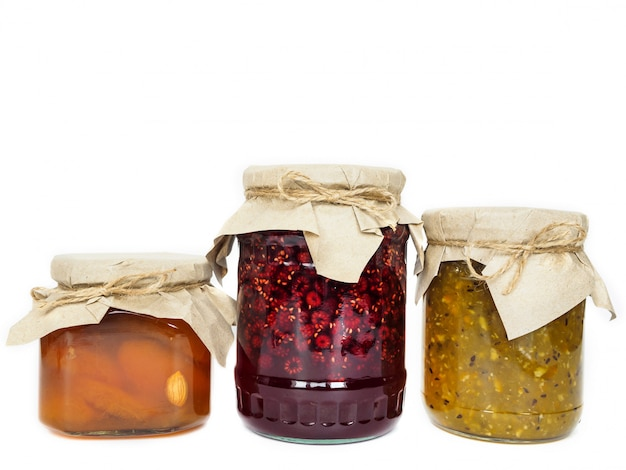 Drei gläser mit unterschiedlicher marmelade auf weißer oberfläche