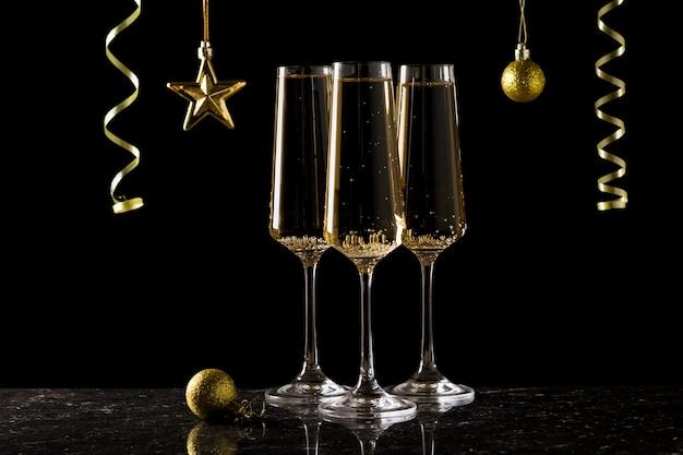 Drei gläser mit wein und schmuck in goldfarbe gefüllt. ein beliebtes alkoholisches getränk.