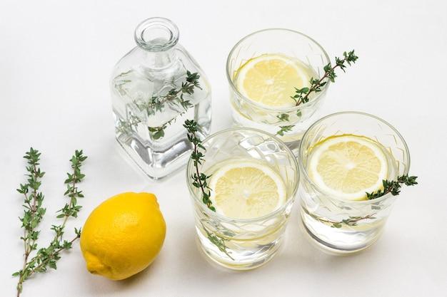 Drei gläser mit zitrone und thymianzweig. zitrone auf dem tisch