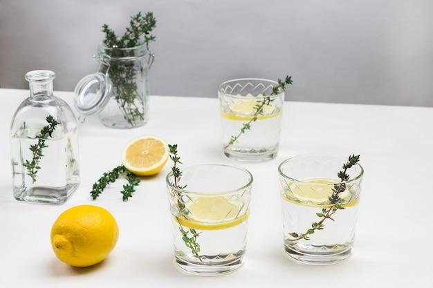 Drei gläser mit zitrone und thymianzweig