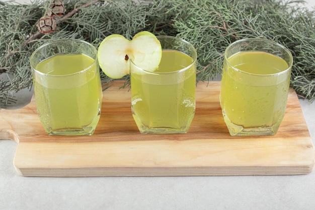 Drei gläser saft mit apfelscheibe auf holzbrett.