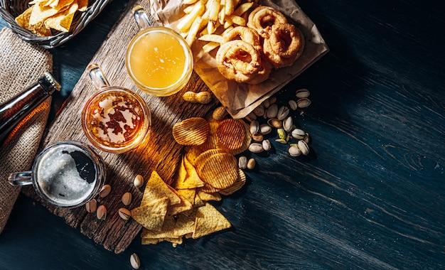 Drei gläser teures craft beer, klassisch und ungefiltert und dunkel in einem glas auf dem tisch mit einem snack aus erdnuss- und pistazienchips und nachos