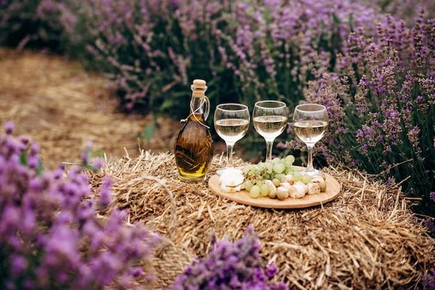 Drei gläser weißwein, vorspeisenkäse, trauben, biscotti, olivenöl und ein blumenstrauß auf einem heuhaufen zwischen lavendelbüschen. romantisches picknick. weicher selektiver fokus.