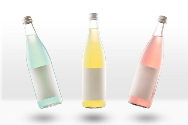 Drei glasflaschen limonade und kohlensäurehaltige getränke mit leeren modelletiketten. gelb, pink und hellgrün. leer für designer