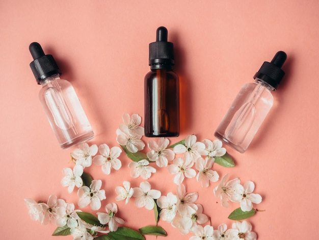 Drei glasflaschen mit öl, parfüm auf rosa oberfläche mit blühender kirsche. flache lage, minimalismus.