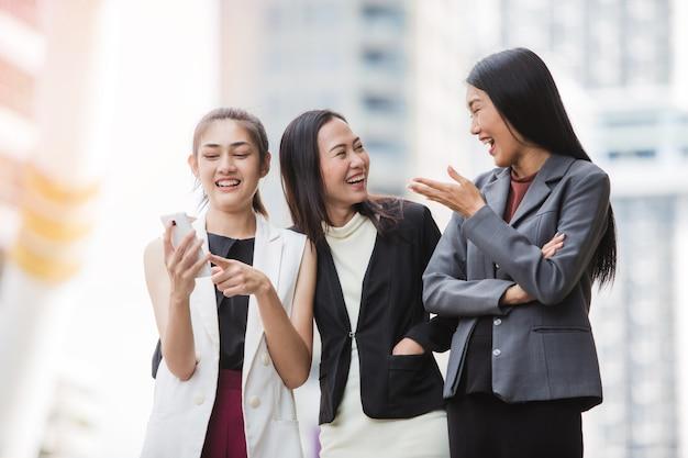 Drei glückliche büromädchen, die smartphone vor dem bürogebäude betrachten