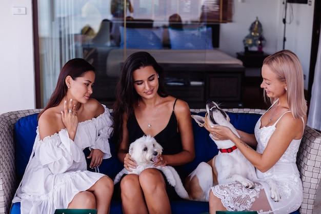 Drei glückliche frau, die auf sofa mit hunden entspannt