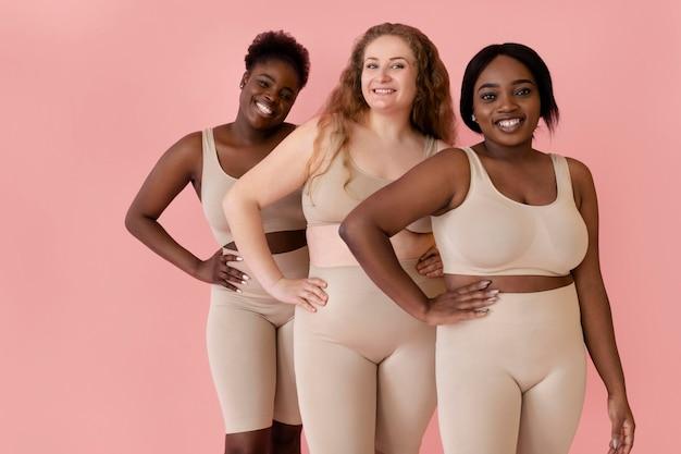 Drei glückliche frauen, die posieren, während sie einen körperformer tragen