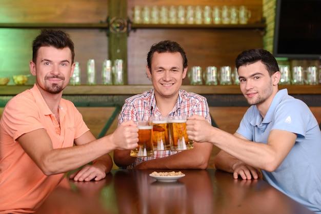 Drei glückliche freunde, die bier an der kneipe trinken.