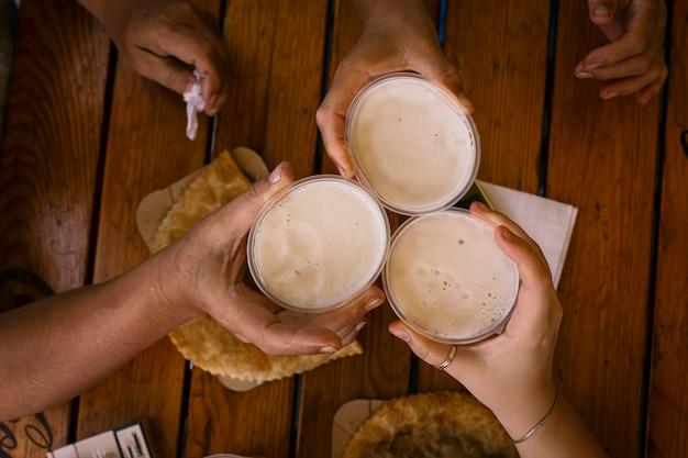 Drei glückliche freunde, die bier trinken und bier rösten. freundschaftskonzept mit jungen leuten, die spaß zusammen an coolem weinlese-pub haben.