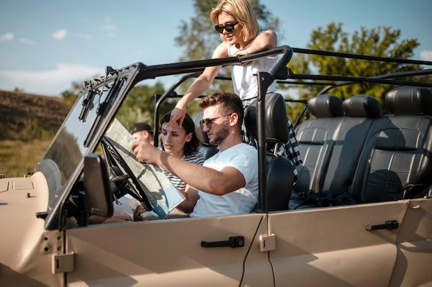 Drei glückliche freunde, die karte während der fahrt mit dem auto überprüfen