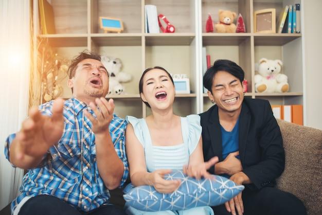 Drei glückliche freunde, die sprechen und großes lachen, nachdem sie witzgeschichte beobachtet haben
