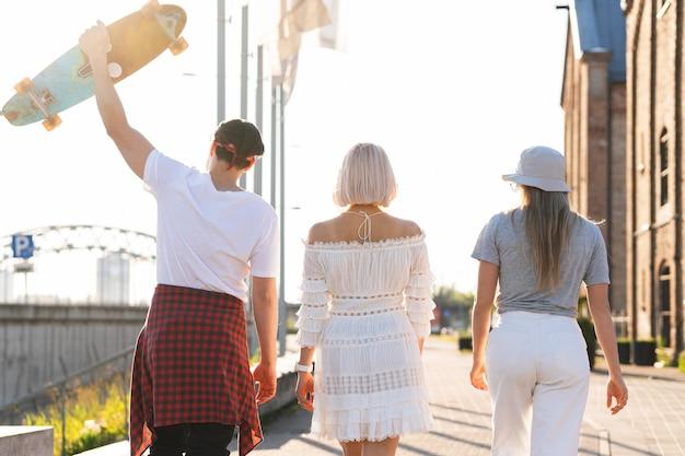 Drei glückliche freunde im teenageralter, die in eine stadt gehen