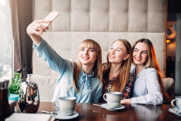 Drei glückliche freundinnen machen selfie auf telefonkamera im café. freundinnen sitzen im restaurant und haben spaß, klatsch treffen