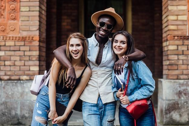 Drei glückliche internationale studenten in der nähe der universität auf dem campus