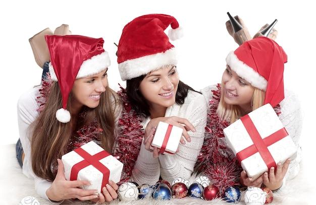 Drei glückliche junge frauen im kostüm des weihnachtsmannes mit weihnachtsgeschenken