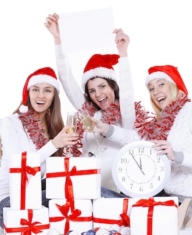 Drei glückliche junge frauen in den hüten des weihnachtsmannes mit uhr und leerem plakat, die zu weihnachten gratulieren