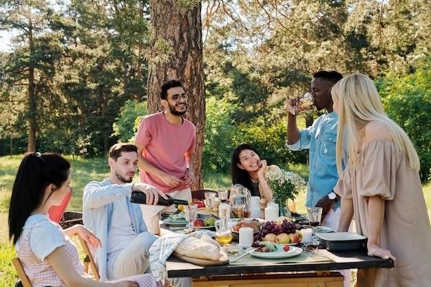 Drei glückliche junge interkulturelle paare besprechen, was sie nach dem abendessen im freien tun werden, während sie am servierten tisch sitzen