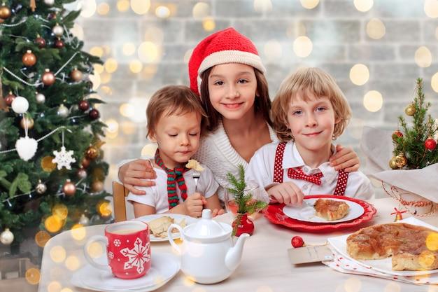 Drei glückliche kinder, die einen weihnachtsapfelkuchen essen