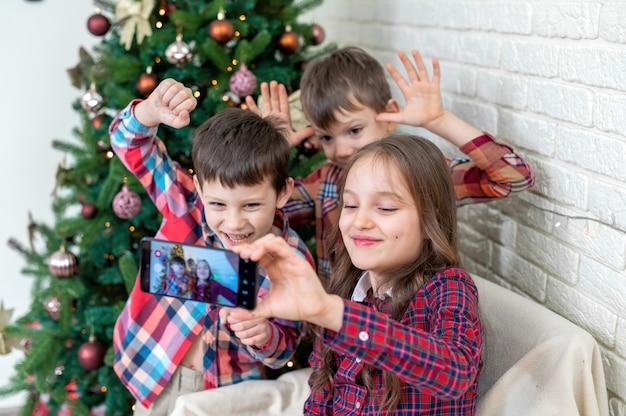 Drei glückliche kinder machen selfie in der nähe des weihnachtsbaumes. glückliche familie
