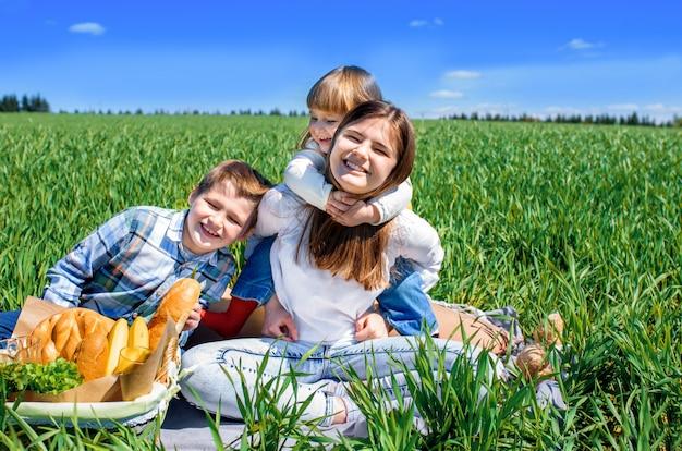 Drei glückliche kinder sitzen auf picknick auf dem feld. blauer himmel, grünes gras. brot, kuchen und obst in einem korb.