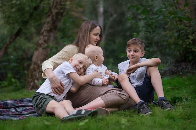 Drei glückliche lächelnde kinder, die im park mit mutter sitzen. familienpicknick