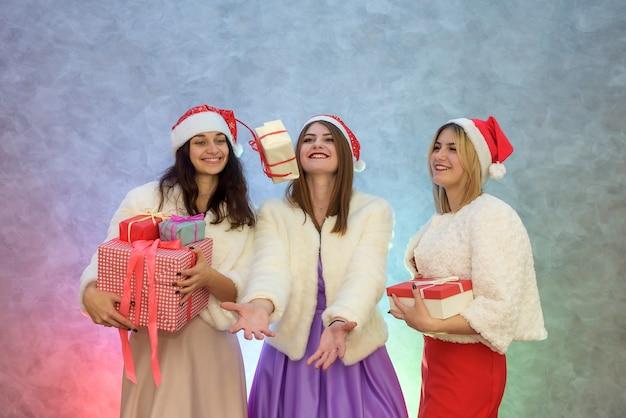 Drei glückliche mädchen, die ihre geschenkboxen hochwerfen. sie sind in eleganten kleidern und pelzjacken
