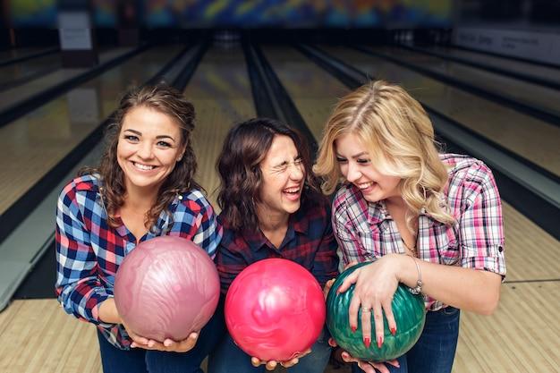 Drei glückliche mädchen, die mit bowlingkugeln im verein aufwerfen.